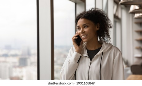 Close up smiling African American woman talking on smartphone, standing near panoramic window at home, enjoying pleasant conversation with friend or boyfriend, holding smartphone, making phone call