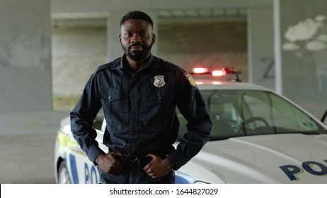 Close up smiling african american young man cops stand near patrol car look at camera enforcement happy officer police uniform auto safety security communication control policeman portrait slow motion