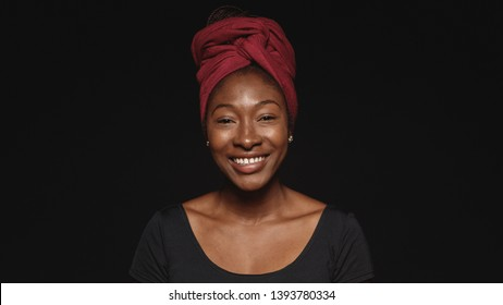 Close up of smiling african woman isolated on black background. African female with a cloth wrapped on head looking at camera.