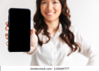 Close up of a smiling asian businesswoman showing blank screen mobile phone isolated