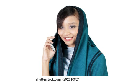 Close up of smiling Asian muslim girl having conversation on smartphone, isolated on white background