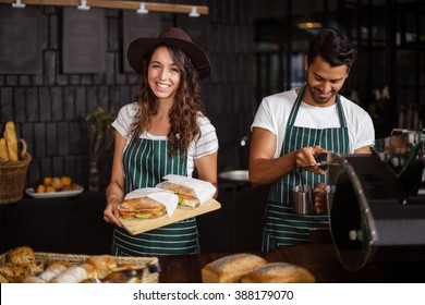 Close up of smiling baristas holding sandwiches and making coffee in the bar