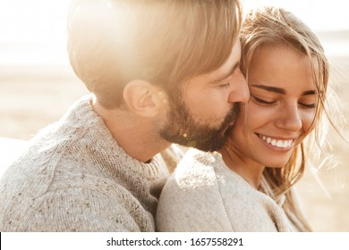 Close up of a smiling beautiful young couple embracing while standing at the beach