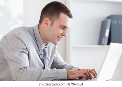 Close up of smiling businessman writing an email with his laptop