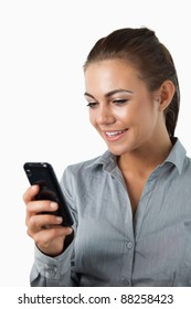 Close up of smiling businesswoman reading text message against a white background