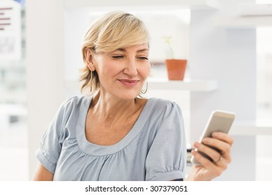Close up of a smiling businesswoman sending a text at office