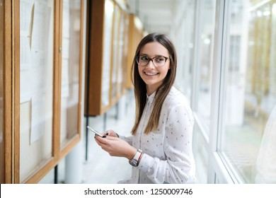 Close up of smiling Caucasian female student with eyeglasses and brown hair using smart phone while standing next to noticeboard.