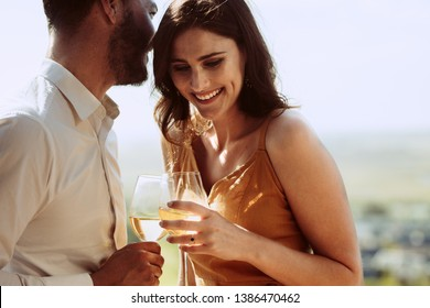 Close up of a smiling couple standing together holding wine. Man talking in to the ear of his girlfriend while on a wine date.