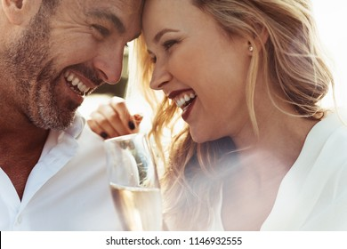 Close up of smiling couple with their heads touching and laughing. Loving couple with wine enjoying each others company.