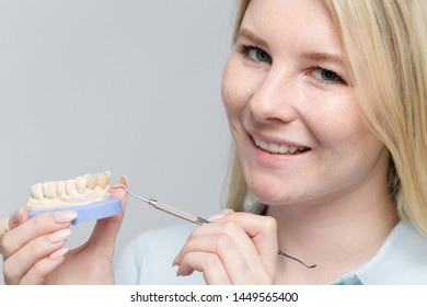 close up of smiling dental technician working on denture parts