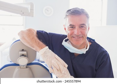 Close up of smiling dentist leaning against dentists chair in dental clinic
