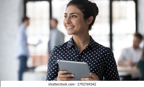 Close up smiling dreamy Indian businesswoman holding computer tablet, looking to aside, intern thinking about new job opportunities, startup ideas, dreaming about good future, business success