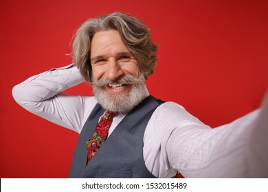 Close up of smiling elderly gray-haired mustache bearded man in classic shirt vest and tie isolated on red background. People lifestyle concept. Mock up copy space. Doing selfie shot on mobile phone