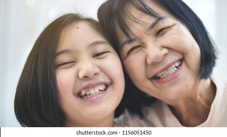 Close up smiling face of happy Asian girl hugging her grand mother, Multi generation of Asian female