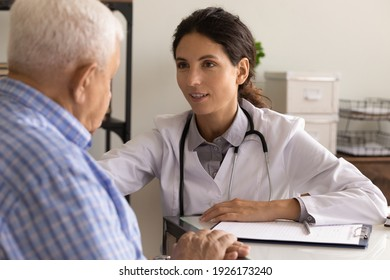 Close up smiling female physician wearing uniform with stethoscope comforting mature patient, sharing good news, medical checkup results, doctor consulting older man at meeting, healthcare concept