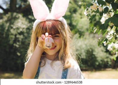 Close up of a smiling girl holding a painted easter egg in front of her face. Girl wearing rabbit ear headband having fun playing with painted eater egg.