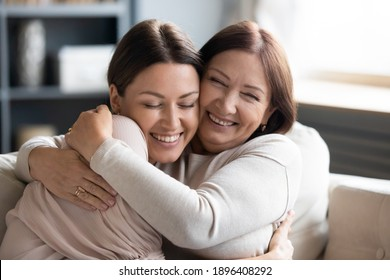 Close up smiling grownup daughter and mature mother cuddling, enjoying tender moment, hugging, expressing love, having fun, sitting on cozy couch at home, family spending leisure time together