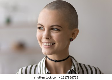 Close up of smiling hairless millennial punk girl look in window distance dreaming thinking. Dreamy bald young creative Caucasian woman lost in thoughts pondering or planning. Art, vision concept.