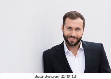Close up Smiling Handsome Middle Age Businessman in Black and White Suit Leaning on White Wall.