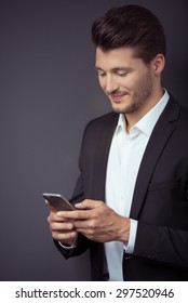 Close up Smiling Handsome Young Businessman Using his Mobile Phone Against Gray Wall Background.