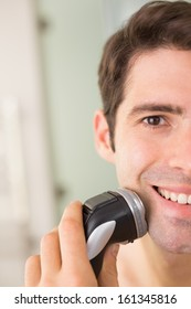 Close up of a smiling handsome young man shaving with electric razor