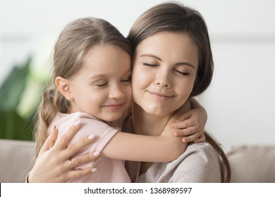 Close up smiling loving attractive mother little daughter girl closed eyes enjoy moment of unity and caress, younger older sisters cuddling showing devotion love, new mom for orphan kid concept image
