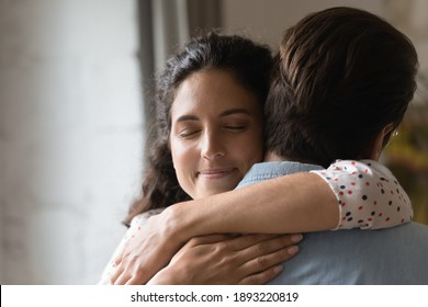 Close up smiling loving wife with closed eyes hugging husband, family, spouses enjoying tender moment, standing at home, happy attractive girlfriend and boyfriend embracing, romantic relationship