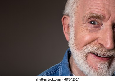 Close up of smiling man half face expressing positive emotions. Copy space in left side. Isolated on grey background