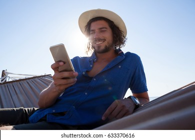 Close up of smiling man using mobile phone while relaxing on hammock at beach during sunny day