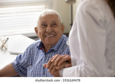 Close up smiling mature man and female caregiver wearing white uniform holding hands, doctor nurse comforting and supporting senior patient at meeting in hospital, expressing empathy and care