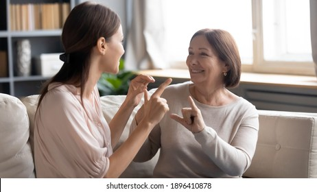 Close up smiling mature mother and grownup daughter speaking sign language, sitting on couch, young woman with elderly mum enjoying pleasant conversation, communicating, showing gestures, deaf family