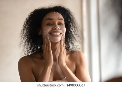 Close up of smiling mixed race ethnicity young woman look in mirror apply facial moisturizing mask, positive african American female massage face do skincare beauty anti-aging treatment in bathroom