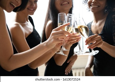 Close up of smiling multiethnic classy ladies in black dresses cheers drink champagne enjoy bridal shower, happy diverse millennial girls in gowns celebrate hen party or bachelorette night at home