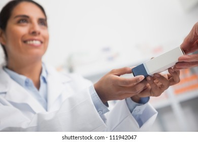 Close up of a smiling pharmacist giving a box to someone in hospital ward