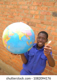 Close  up of  a smiling  primary  schoolkid in  school  uniform  holding  a  globe  world  map  in  one  hand  whilst  the  other  shows  a  thumbs  up  sign  in  front  of  a brickwall.