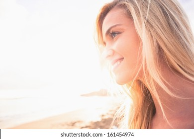 Close up of a smiling relaxed young blond looking away at the beach