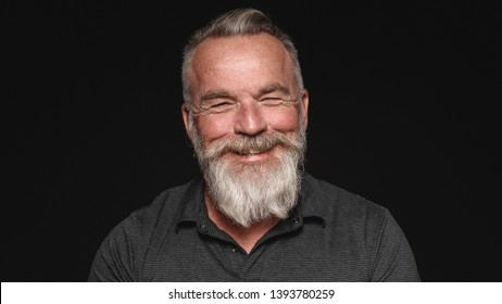 Close up of smiling senior man with a white beard. Portrait of a senior man isolated on black background.