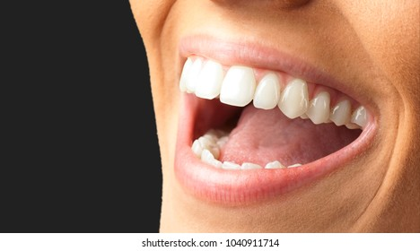 Close Up Of Smiling Teeth against a black background