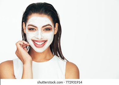 Close up of a smiling woman with cosmetic facial mask applied over her face.