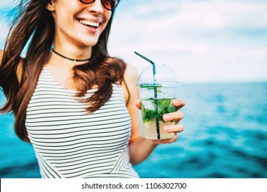 Close up of a smiling woman enjoying a tropical mojito cocktail at the seaside with a straw on her summer vacation