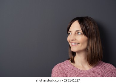 749e4ea6cfa Close up Smiling Woman Looking to the Left of the Frame Against Gray Wall  Background with