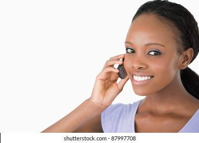 Close up of smiling woman on the phone against a white background