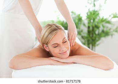 Close up of a smiling woman relaxing on a lounger enjoys a massage in a wellness center