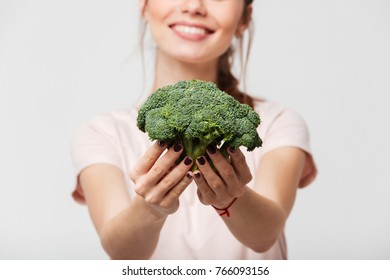 Close up of a smiling woman showing broccoli isolated over white background