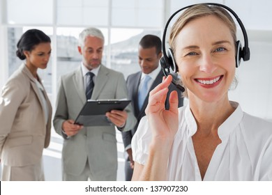Close up of smiling woman standing with a headset with colleagues working behind
