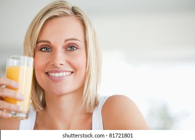 Close up of a smiling woman toasting with orange juice in the kitchen