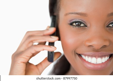 Close up of smiling woman using her mobile phone on white background
