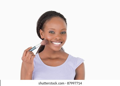 Close up of smiling woman using make-up brush against a white background