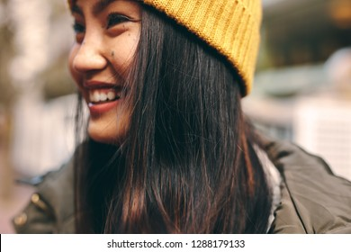Close up of a smiling woman in winter clothes standing outdoors. Cropped shot of a smiling asian woman in winter cap standing outdoors.