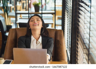 Close up smiling young Asian woman in formal suit sitting in front of laptop on wooden table take a rest on brown sofa chair next the winndow at brown tone modern office.